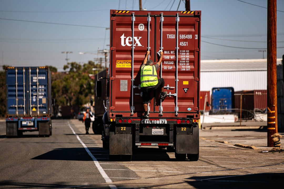 A truck driver checks his cargo as the Port of Los Angeles is set to begin operating around the clock.