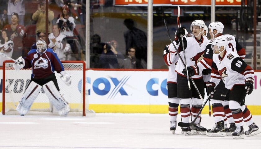 Arizona Coyotes' Nicklas Grossmann (2), of Sweden, celebrates with teammates, including Connor Murphy, left, Mikkel Boedker (89), of Denmark, after Grossmann scored a goal against Colorado Avalanche's Semyon Varlamov, left, of Russia, during the first period of an NHL hockey game Thursday, Nov. 5,
