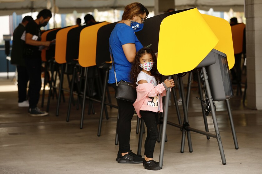 Arabella Abarca, 4, waits patiently as her mom, Alexis Abarca, votes Tuesday at Dodgers Stadium.
