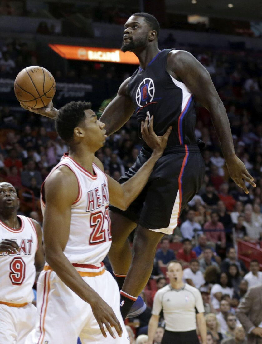 Los Angeles Clippers forward Lance Stephenson, right, goes to the basket as Miami Heat center Hassan Whiteside (21) defends during the first half of an NBA basketball game, Sunday, Feb. 7, 2016, in Miami. (AP Photo/Lynne Sladky)