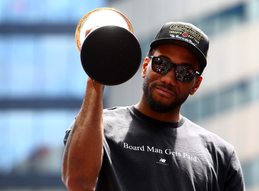 Kawhi Leonard of the Toronto Raptors holds the MVP trophy during the team's victory parade on June 17, 2019, in Toronto, Canada.