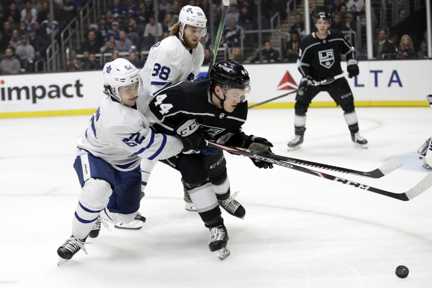 Kings defenseman Mikey Anderson fights for position against Maple Leafs center Denis Malgin during the third period of a game March 5 at Staples Center.