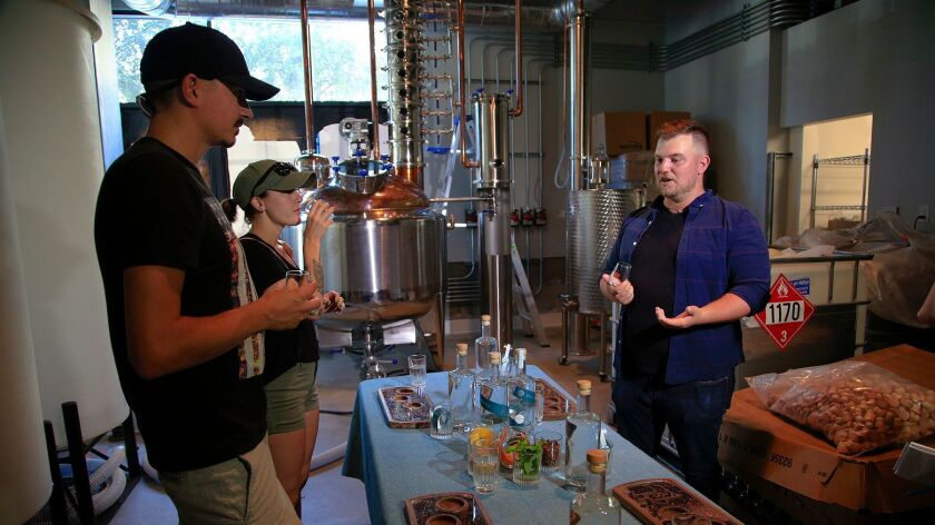At the You & Yours Distilling Co., bar and distillery manager Trevor Bowles (right) explains the difference between vodka and gin to Daniel McCullough and Nea Muller. The new East Village distillery now offers tours, which include a spirits tasting.