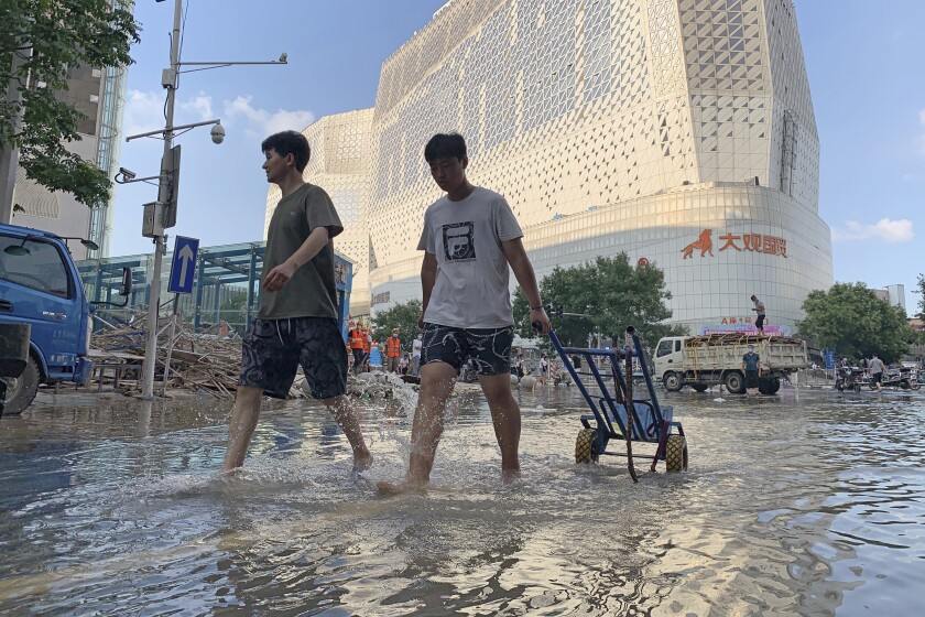 Residents walk along a flooded road in the aftermath of the heaviest recorded rainfall in Zhengzhou in central China's Henan province on Saturday, July 24, 2021. Rescuers used bulldozers and rubber boats to move residents out of flooded neighborhoods in central China on Saturday after torrential rains killed at least 56 people. (AP Photo/Dake Kang)