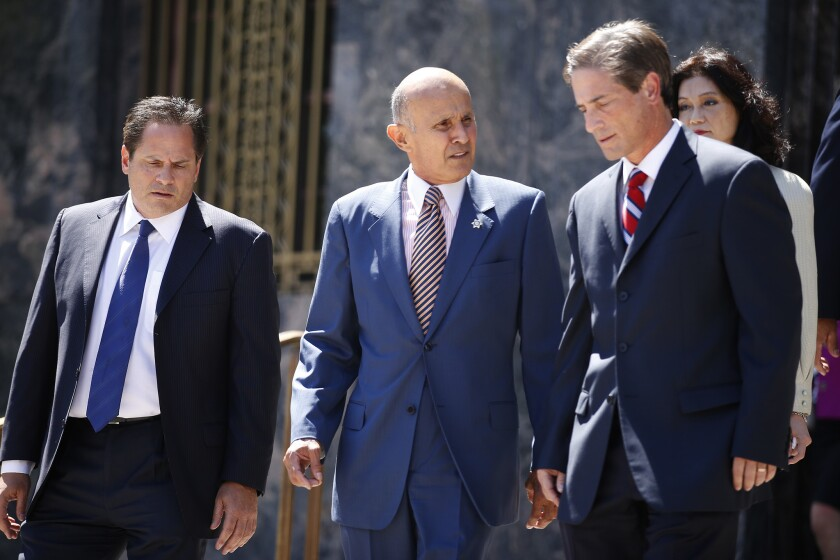 Flanked by his attorneys, former Los Angeles County Sheriff Lee Baca leaves federal court in Los Angeles earlier this year after being arraigned on charges of conspiracy, obstructing justice and lying to the federal government.