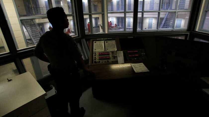 Sheriff's deputy Lee Lee looks over a holding block inside the Fresno County jail.