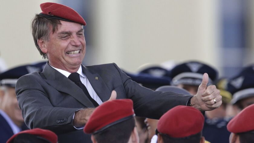 Far-right Brazilian presidential candidate Jair Bolsonaro flashes two thumbs up as he poses for a photo with cadets during a ceremony marking Army Day on April 19, 2018 in Brazil.