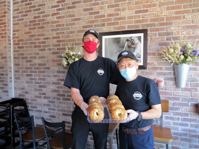 Owner Jeffrey Wang, right, and his apprentice bagel-maker Jacob Lynch hold a tray of everything bagels, the best-selling product at newly opened Solomon Bagels & Donuts in North Park on Tuesday, April 28. Despite the challenges of opening April 17, during the pandemic, the shop has been very busy.