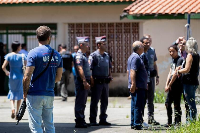 Police officers stand guard at a school in Suzano, Brazil, hours after a school shooting on March 13, 2019, that left 10 dead, including the two perpetrators, and 11 wounded. EPA-EFE/File