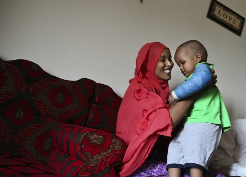 Fadumo Abudllahi holds her son Musa, 16, months, at their home Wednesday, June 11, 2014 in Minneapolis. Musa Dayib survived an 11-story fall from their home in a Minneapolis high-rise a month ago. Doctors will remove his last cast Thursday, the one covering his left arm from the wrist to the biceps. The only other visible sign of his fall is a pink scar on the back of his head. (AP Photo/The Star Tribune, David Joles) MANDATORY CREDIT; ST. PAUL PIONEER PRESS OUT; MAGS OUT; TWIN CITIES TV OUT