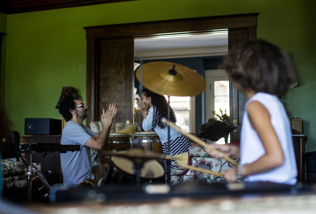 Gabe Roth teaches rhythm to Allison Furbush while his son Sylvester Roth keeps the beat on the drums during music class.