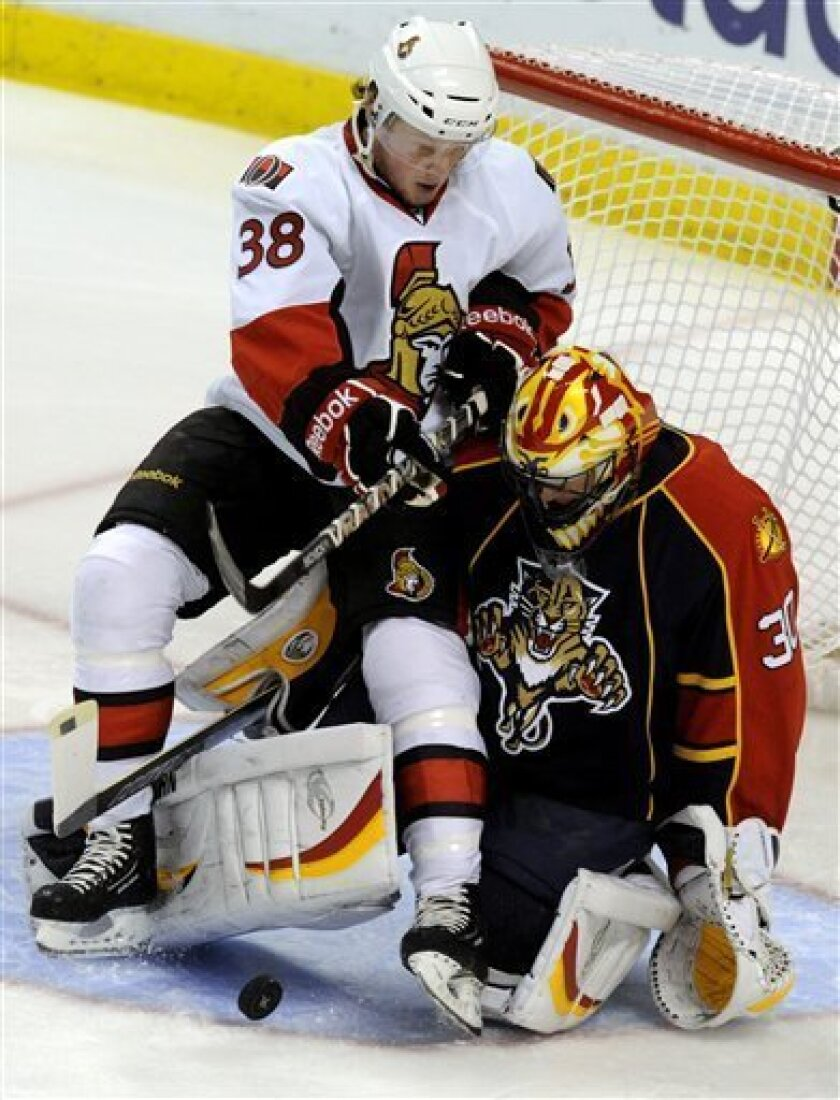 Ottawa Senators' Erik Condra, left, trips backward over Florida Panthers goalie Scott Clemmensen  who makes the save during the first period of an NHL hockey game on Thursday, March 31, 2011, in Sunrise, Fla. (AP Photo/Rick Silva)
