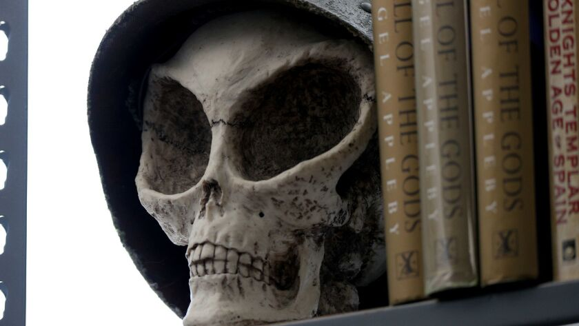 A rendition of what an alien skull may look like acts as a book end in library of the Mutual UFO Net