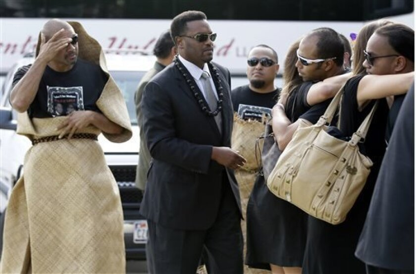 "David Eteaki, left, looks on as Texas A&M football head coach Kevin Sumlin, center, family, and members of his team are greeted at a receiving line before the start of a funeral service for redshirt freshman Polo Manukainiu and his brother Andrew Uhatafe, at the Church of Jesus Christ Of Latter Day Saints, Saturday, Aug. 10, 2013, in Colleyville, Texas. The two were killed in a single car accident in Northern New Mexico, July 29. Also killed was 18-year-old Utah recruit Gaius ""Keio"" Vaenuku. (A"