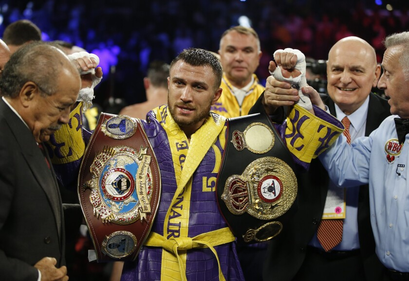 FILE - In this April 12, 2019, file photo, Vasiliy Lomachenko celebrates defending his WBA/WBO lightweight titles after knocking out Anthony Crolla, in Los Angeles. Lomachenko fights Teofimo Lopez on Saturday, Oct. 17, 2020, in Las Vegas. Boxing fans should be thankful. They're getting a quality fight _ and they're getting it for free.(AP Photo/Damian Dovarganes, File)