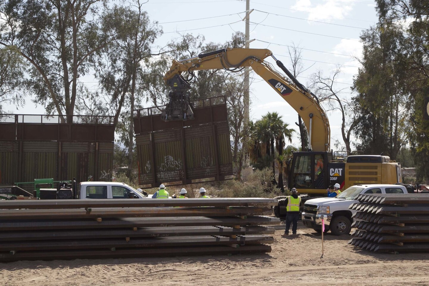 An excavator with a special clamp removes a section of the 1990'a era metal fence west of the Calexico Port of Entry that will be replaced with a steel bollard style structure that will be higher than the previous one.