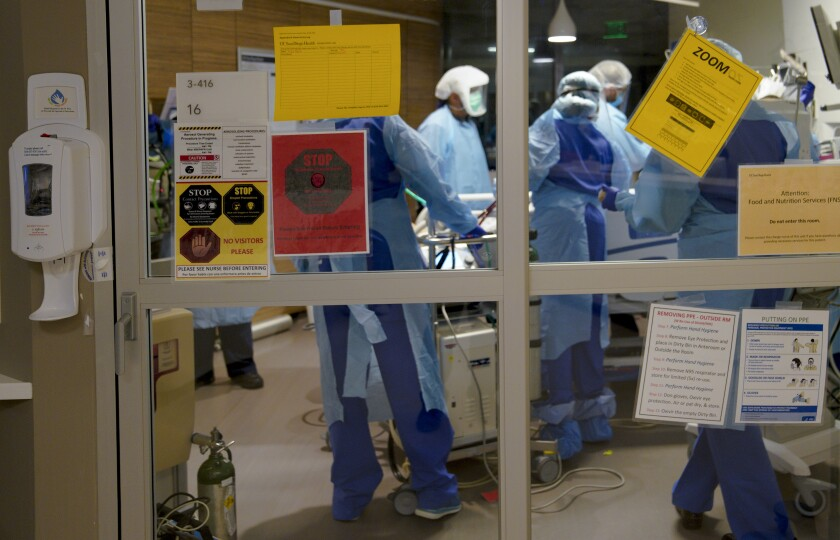 Health care workers tend to a patient with COVID-19 in the intensive care unit at UCSD Jacobs Medical Center in June 2020.