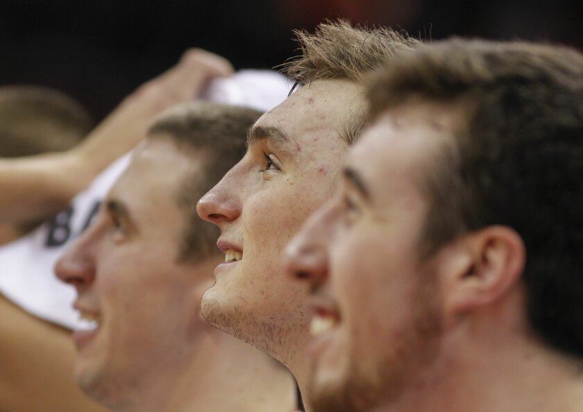 Wisconsin's Josh Gasser, left, Sam Dekker and Frank Kaminsky, right, watch the final minutes of play against Prairie View in an NCAA college basketball game Saturday, Dec. 28, 2013, in Madison, Wis. Dekker had a game-high 16 points in Wisconsin's 80-43 win. (AP Photo/Andy Manis)