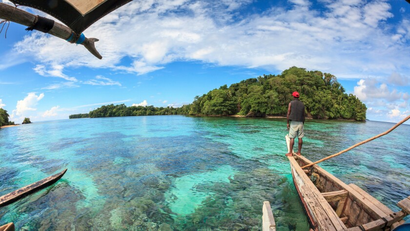 A Titan villager navigates a traditional Melanesian outrigger over the coral reef surrounding the island of Mbuke in Papua New Guinea.
