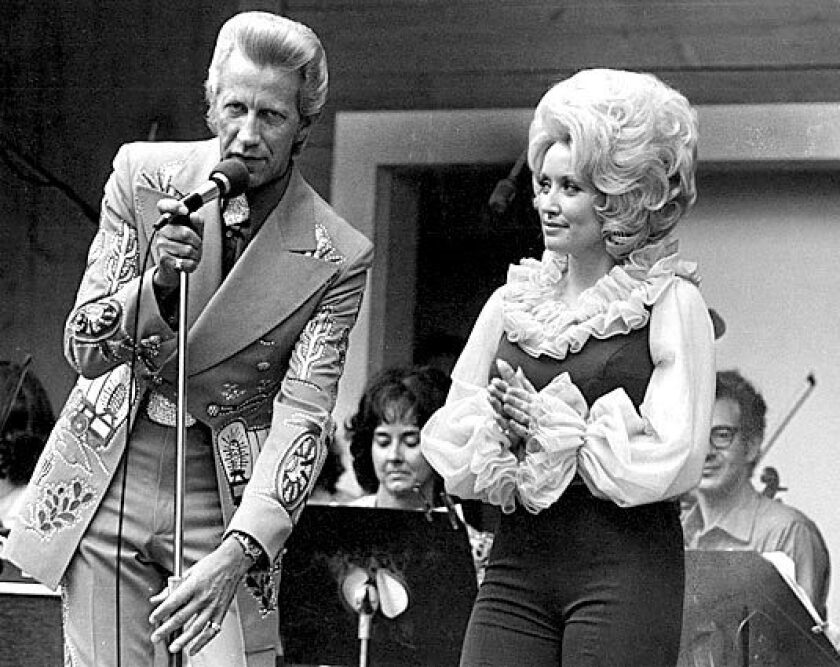 Country music stars Porter Wagoner and Dolly Parton perform at Opryland U.S.A. in 1975. Parton was on Blackwell's list four times between 1978 and 1981.