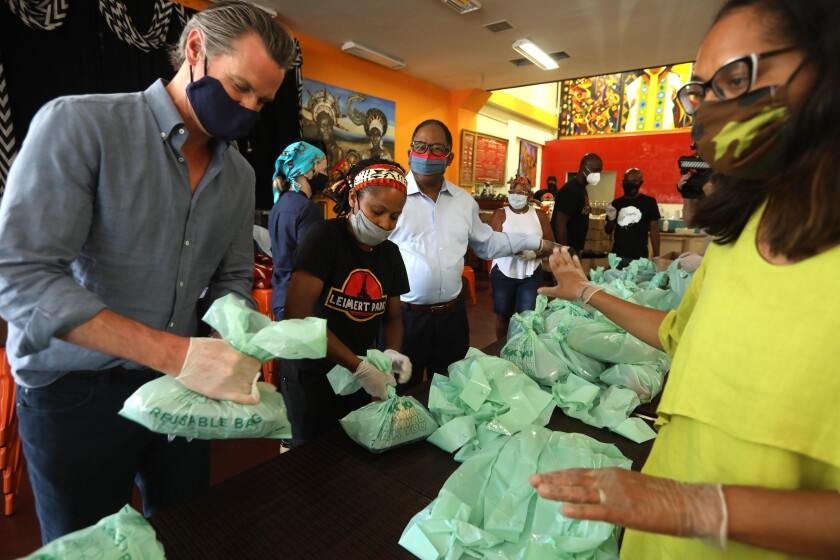 Gov. Gavin Newsom helps pack up lunches to be delivered to senior citizens at Hot & Cool Cafe in Leimert Park on Wednesday.