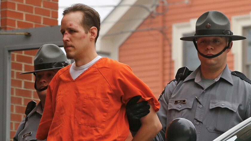 Police escort Eric Frein into the Pike County Courthouse for his arraignment in Milford, Pa., on Oct. 31, 2014.