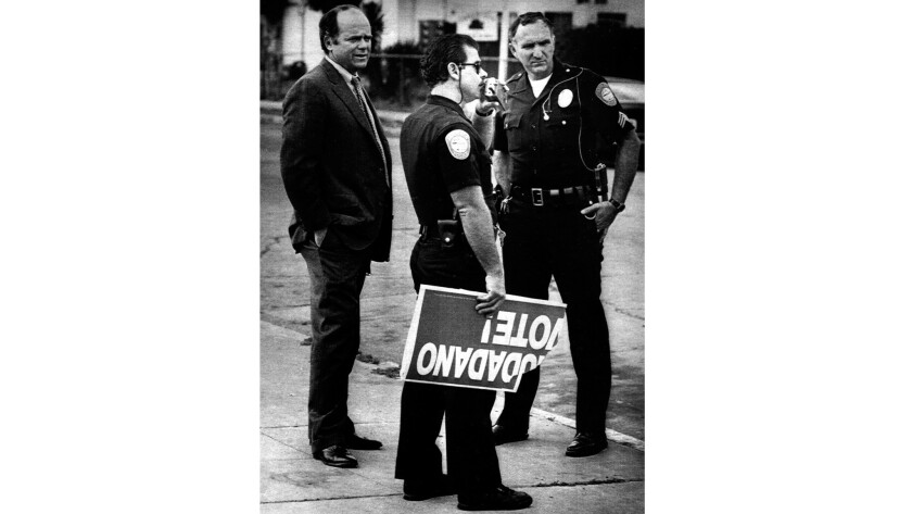 A police officer holds part of a sign discouraging people to vote.