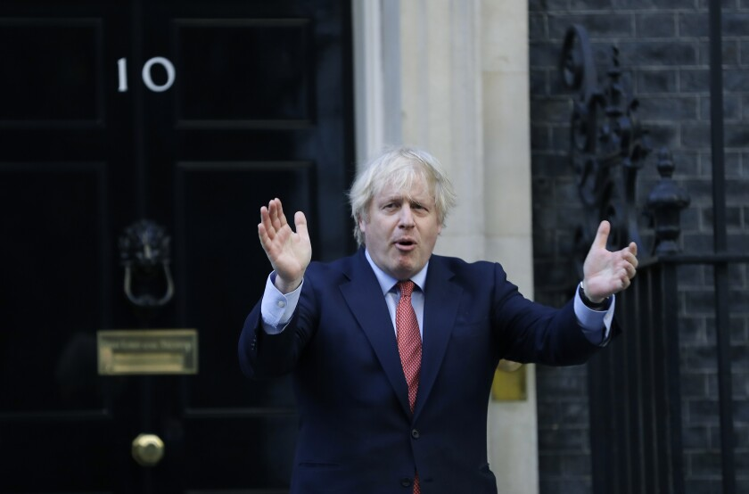 FILE - In this file photo dated Thursday, May 28, 2020, Britain's Prime Minister Boris Johnson applauds on the doorstep of 10 Downing Street in London. Johnson has said his government will introduce White House-style televised press briefings, in a shakeup to the traditional system of political communication, reports The Financial Times on Friday July 3, 2020. (AP Photo/Kirsty Wigglesworth, FILE)