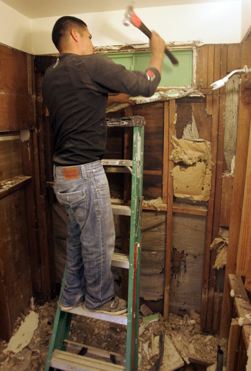 Juan Lopez works in the bathroom of a home in Paradise Hills being prepared for sale by RDB Ventures.