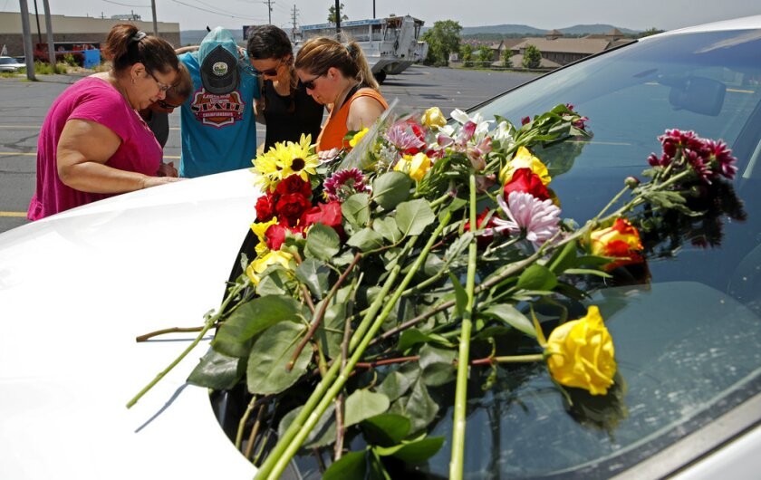 People pray next to a car believed to belong to a victim of a last night's duck boat accident, Friday, July 20, 2018 in Branson, Mo. The country-and-western tourist town of Branson, Missouri, mourned Friday for more than a dozen sightseers who were killed when a duck boat capsized and sank in stormy weather in the deadliest such accident in almost two decades.