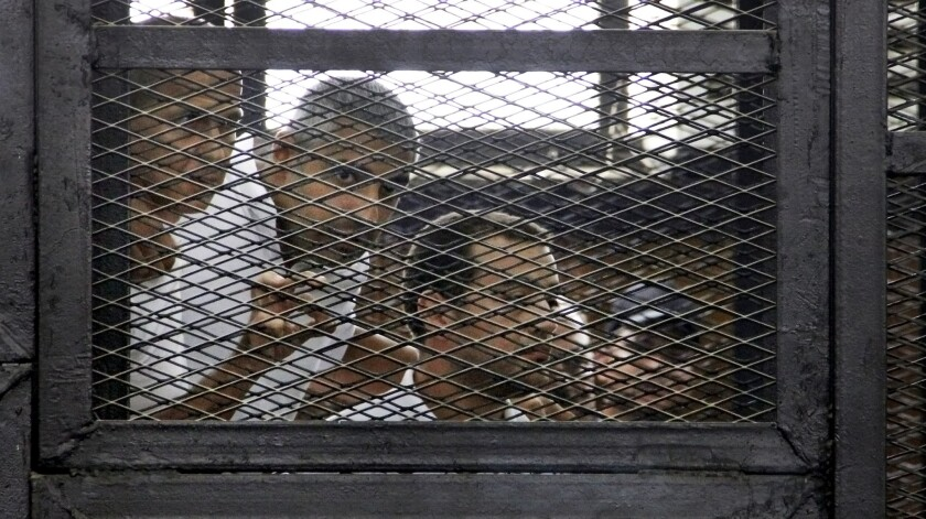 From left, Al Jazeera journalists Peter Greste, Mohamed Fahmy and Baher Mohamed appear in the defendant's cage in an Egyptian courtroom on Monday.