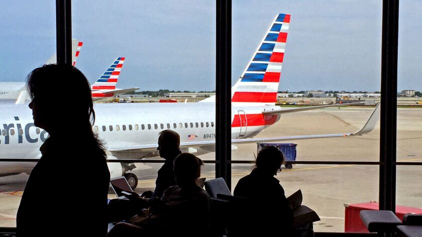 """Travelers at Chicago O'Hare International Airport await their flights at the American Airlines terminal. The airline has unveiled a """"basic economy"""" fare to compete with low-cost carriers."""