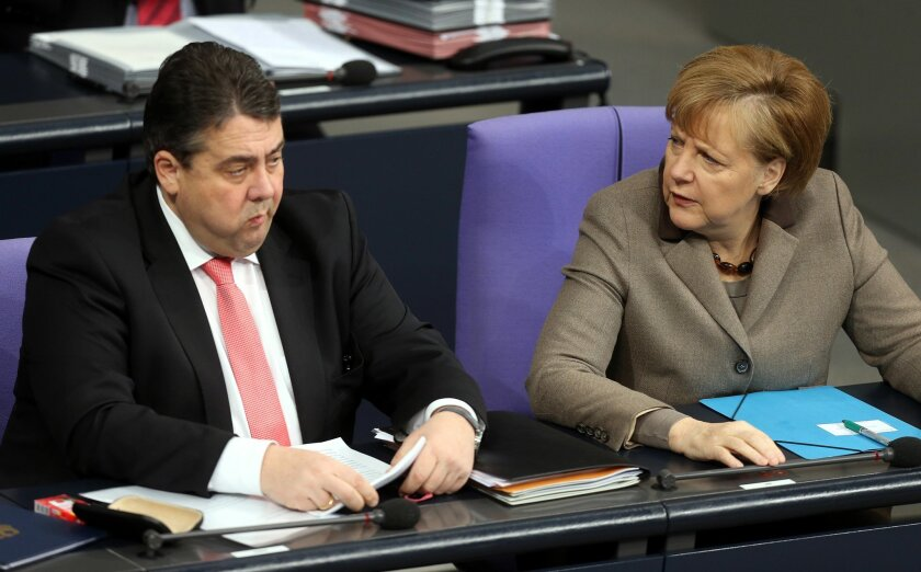 FILE - In this Jan. 30, 2014 file photo German Economy Minister Sigmar Gabriel from the Social Democrats and Chancellor Angela Merkel, from left, attend a session at the German parliament Bundestag in Berlin, Germany. Germany's two-month-old government is facing its first serious test, after old enmities between Chancellor Merkel's conservative bloc and their center-left coalition partners flared over the handling of a child pornography investigation. (AP Photo/dpa, Wolfgang Kumm, file)