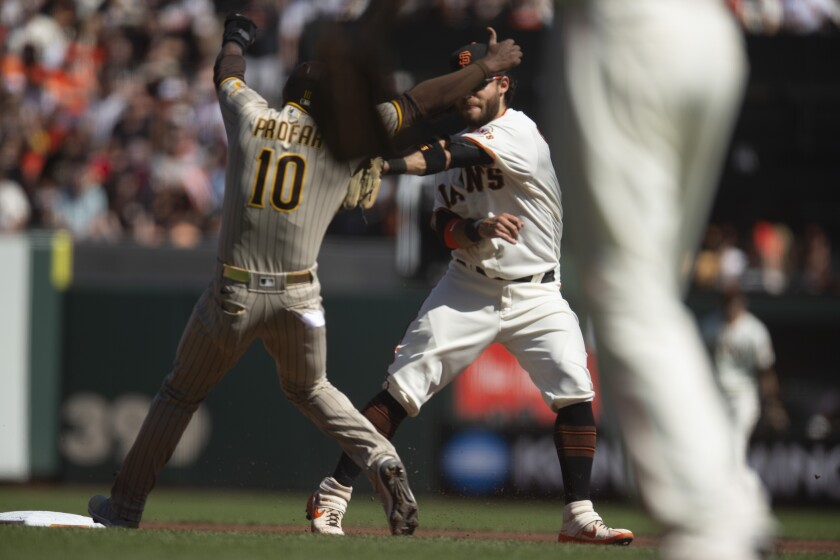 San Francisco Giants shortstop Brandon Crawford, back right, tags out San Diego Padres' Jurickson Profar (10) to complete a double play during the second inning of a baseball game, Saturday, Oct. 2, 2021, in San Francisco. Padres' Ha-Seong Kim was out at first base. (AP Photo/D. Ross Cameron)