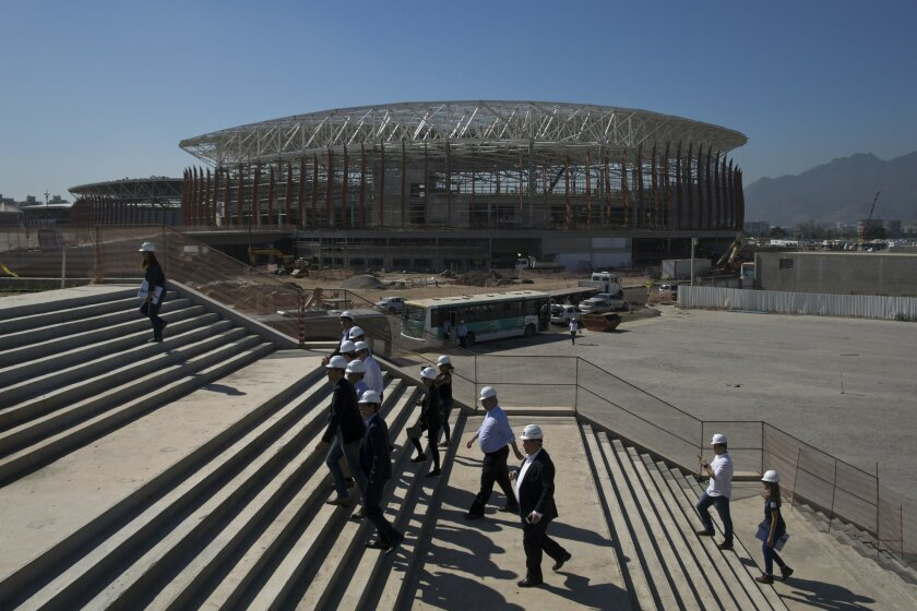 FILE - In this June 11, 2015, file photo, the Arena Carioca 1 is seen in the background as officials visit the Olympic Park of the 2016 Olympics in Rio de Janeiro, Brazil. Hundreds of thousands of foreign visitors are expected for the Olympics, which open Aug. 5. 2016. But there are growing concern