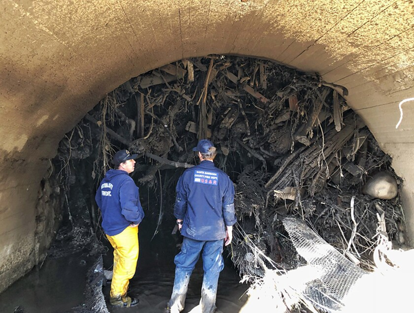 On Jan. 15, Santa Barbara County firefighters survey a wall of debris jammed under a bridge from the deadly rains and mudflow of Jan. 9 in Montecito.