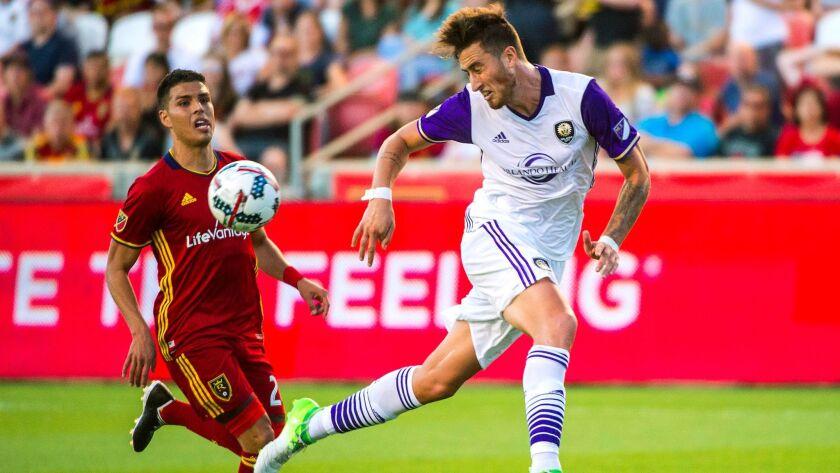 Orlando City defender Jose Aja (4) and Real Salt Lake midfielder Luis Silva (20) go for the ball dur