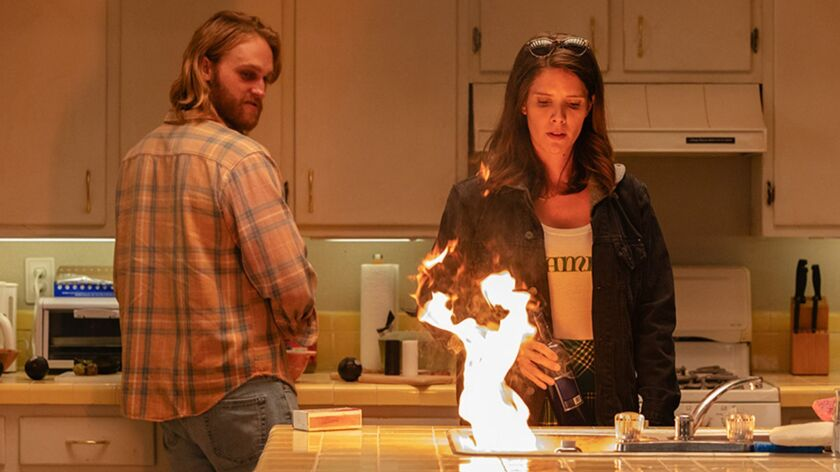 "Wyatt Russell and Sonya Cassidy looking at a counter top fire in ""Lodge 49."""