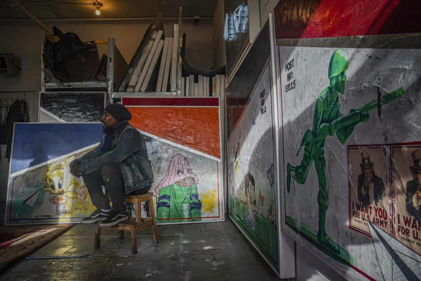 """Painter Guy Stanley Philoche, a 43-year-old Haitian immigrant and star in the New York art world, sit among some of his latest work during an interview at his East Harlem studio, Thursday Nov. 19, 2020, in New York. After a hugely successful gallery show, Philoche wanted to treat himself to a fancy $15,000 watch, instead he bought the works of fellow artists struggling in the pandemic. """"I'm not a rich man,"""" he said, """"but I owe a big debt to the art world."""" (AP Photo/Bebeto Matthews)"""