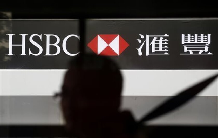 FILE -In this March 4, 2013, file photo, a man walks past the HSBC's Hong Kong headquarters in central district of Hong Kong. HSBC PLC, Europe's biggest bank by market value, said Monday Aug. 5, 2013, that its first half profit rose 22 percent as it reaped the benefits of restructuring measures and reduced loan losses in the United States. Its shares fell, however, on concern about growth in China, a key market. (AP Photo/Vincent Yu, File)