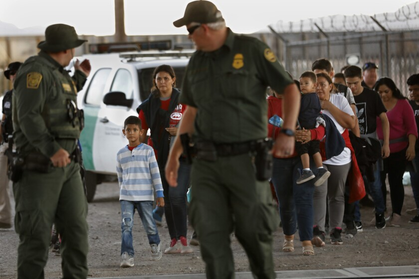 EL PASO, TEXAS--JUNE 21, 2019--A group of about 50 men, women and children are led by U.S. border pa