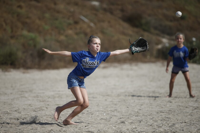 """Scarlett Zuckerman, 7, tracks down a ball hit past her as her team, """"Blondies,"""" faces off against """"The Hot Dogs"""" in the Pee Wee Division."""