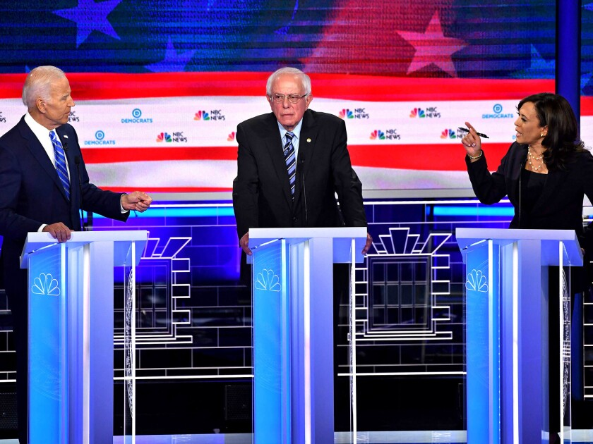 Kamala Harris makes a point to Joe Biden as Bernie Sanders looks on at a Democratic primary debate in June 2019 in Miami.