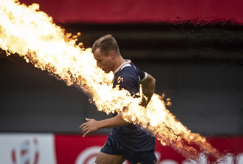 Spain's Enrique Bolinches runs past pyrotechnics before an HSBC Canada Sevens rugby match against Canada in Vancouver, British Columbia, Sunday, Sept. 19, 2021. (Darryl Dyck/The Canadian Press via AP)