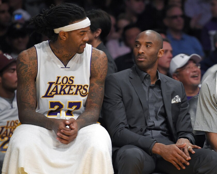Lakers center Jordan Hill and injured shooting guard Kobe Bryant look at each other on the bench during the first half of the Lakers' 100-93 loss to the Mavericks.