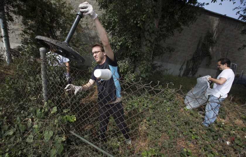 Ryan Murray, left, tosses trash over a fence as a team of volunteers cleans up a vacant lot on Kingsley Drive in East Hollywood in May 2015 in a monthly meet-up organized by the East Hollywood Neighborhood Council.