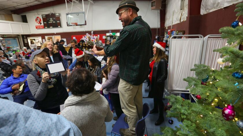 Pastor Ron Zimmer plays Christmas carols for those remaining at his shelter, East Avenue Church, in Chico. The shelter closed Friday.