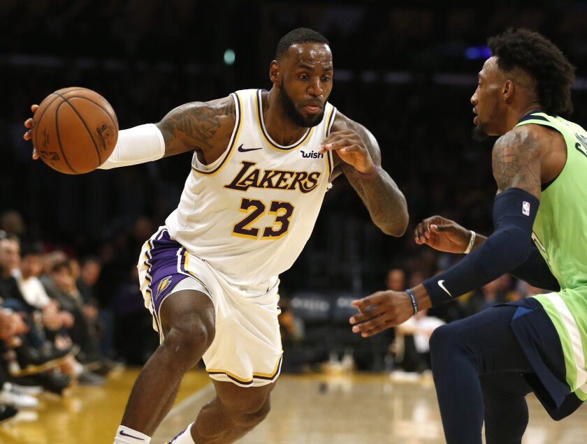Lakers star LeBron James drives around Minnesota Timberwolves forward Robert Covington during the second half of the Lakers' 142-125 win Sunday.