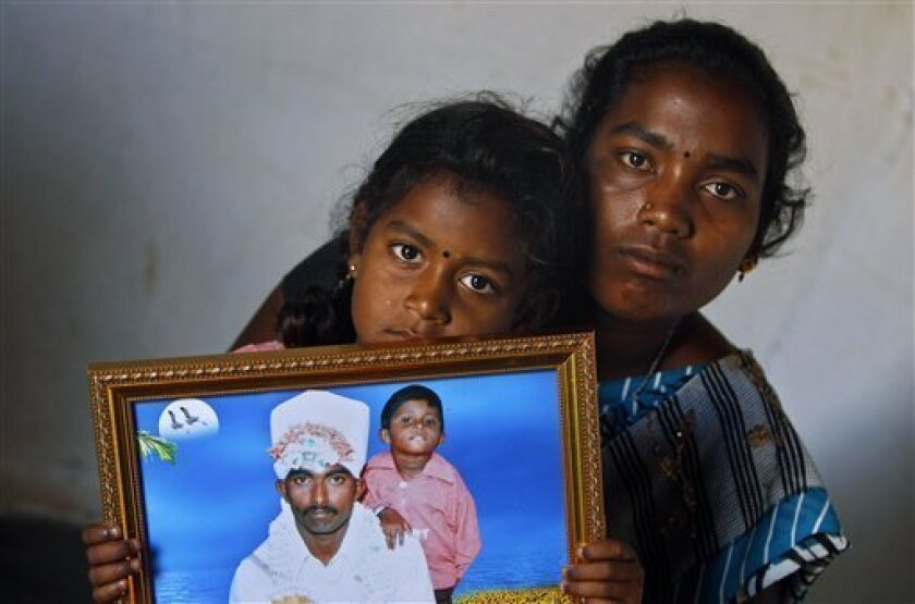 In this photo taken Feb. 14, 2012, Shwetha, 5, sits on the lap of her mother Sunita, 22, as she holds a photograph of her debt-ridden father Hari Prasad, who consumed fertilizer chemical to kill himself on Aug. 1, 2010, in Kadiri village about 160 kilometers (99 miles) north of Bangalore, India. A