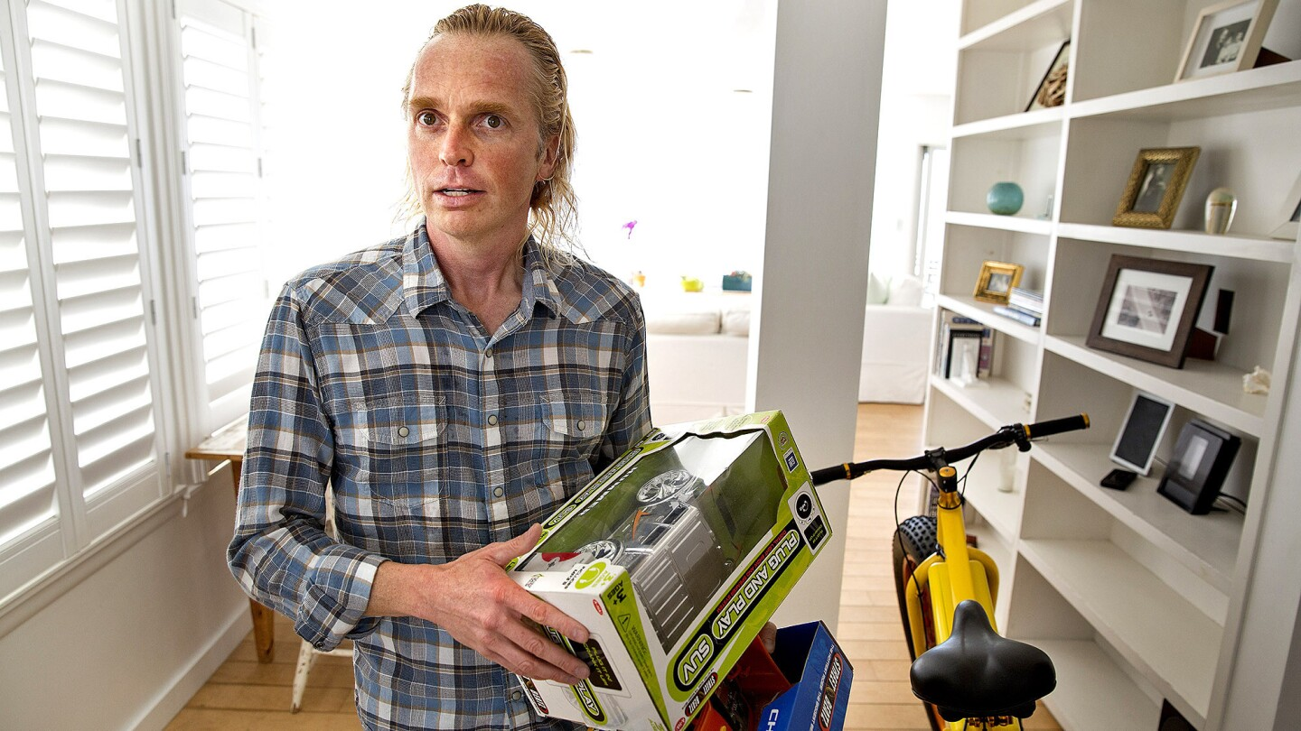 Storm Sonders holds toy cars that he designed at his Malibu home. He was 38 when a therapist identified his condition as Asperger's syndrome three years ago.